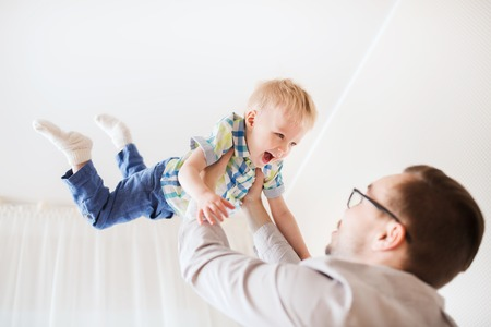 family, childhood, fatherhood, leisure and people concept - happy father and little son playing and having fun at home Stock Photo