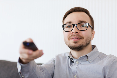 entertainment concept: home, people, technology and entertainment concept - smiling man in eyeglasses with tv remote control at home Stock Photo