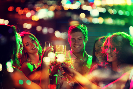 party, holidays, celebration, nightlife and people concept - smiling friends clinking glasses of champagne in night club with holidays lights Stockfoto