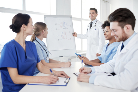 medical education, health care, medical education, people and medicine concept - group of happy doctors or interns with mentor meeting and drawing on flip board on presentation at hospital Banque d'images