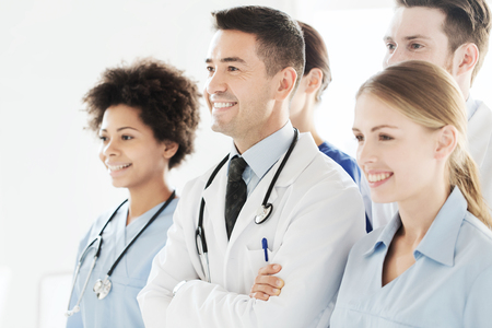 hospital, profession, people and medicine concept - group of happy doctors wit stethoscopes or mentor with interns at hospital Stock Photo