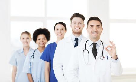 persona feliz: el hospital, la profesión, las personas y la medicina concepto - grupo de médicos felices en el hospital que muestran la muestra aceptable de la mano