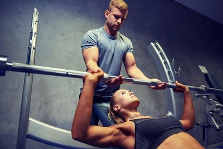 sport, forme physique, le travail d'équipe, la musculation et les gens le concept - jeune femme et un entraîneur personnel avec haltères fléchir muscles dans le gymnase