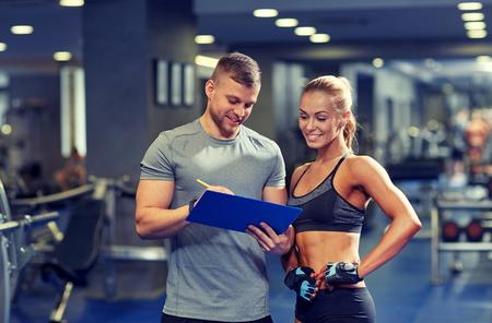 hombre flaco: fitness, deporte, ejercicio y dieta concepto - mujer joven y entrenador personal con el portapapeles escribir plan de ejercicios en el gimnasio sonriendo