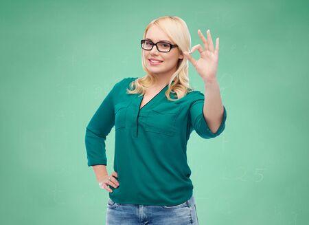 alumnos en clase: la visión, la óptica, la educación, el gesto y la gente concepto - mujer joven sonriente con gafas que muestran bien la escuela sobre fondo verde tarjeta de tiza