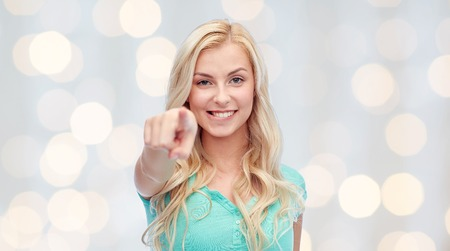gesture and people concept - happy smiling young woman or teenage girl pointing finger to you over holidays lights background