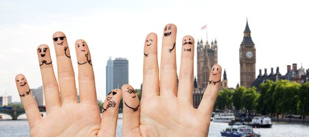 10 fingers: family, wedding, marriage, people and body parts concept - close up of two hands showing fingers with smiley faces over london city background Stock Photo