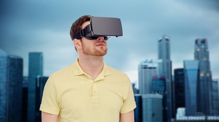 mediated: 3d technology, virtual reality, entertainment and people concept - young man with virtual reality headset or 3d glasses over singapore city skyscrapers background
