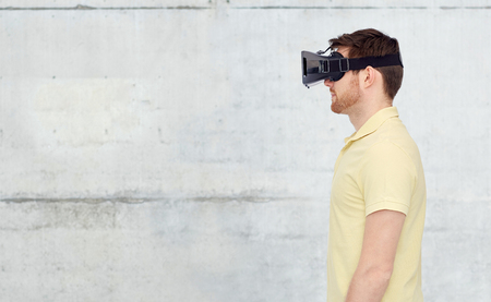 mediated: 3d technology, virtual reality, entertainment and people concept - young man with virtual reality headset or 3d glasses over concrete gray wall background