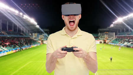 mediated: 3d technology, virtual reality, sport, entertainment and people concept - man in virtual reality headset or 3d glasses playing with game controller gamepad over football field on stadium background