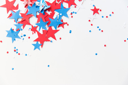 american independence day, celebration, patriotism and holidays concept - red and blue paper stars confetti on american independence day party