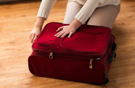 travel bag: summer vacation, travel, tourism and objects concept - close up of woman packing and zipping travel bag for vacation