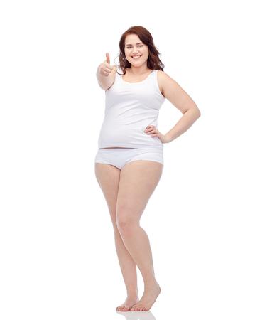 ジェスチャー、重量損失と人々 のコンセプト - プラスサイズの女性の下着親指を見せで若い笑顔 写真素材