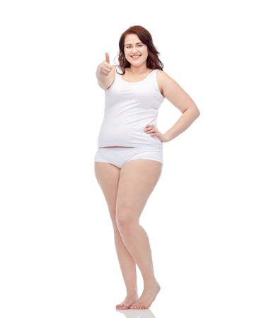 gesture, weight loss and people concept - smiling young plus size woman in underwear showing thumbs up