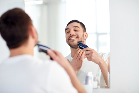 electric shaver: beauty, hygiene, shaving, grooming and people concept - young man looking to mirror and shaving beard with trimmer or electric shaver at home bathroom