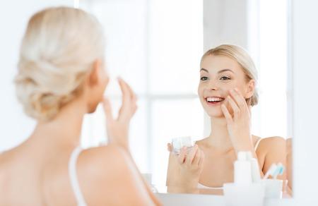 persona feliz: belleza, cuidado de la piel y la gente concepto - mujer joven sonriente aplicar crema en la cara y que mira al espejo en el cuarto de baño casero Foto de archivo