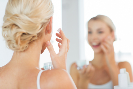 beauty, skin care and people concept - close up of smiling young woman applying cream to face and looking to mirror at home bathroom