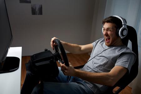tecnología, juegos, entretenimiento y concepto de la gente - hombre joven en auriculares con el equipo de PC juegan carreras de coches videojuegos en el hogar y el volante