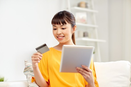 emoney: people, internet bank, online shopping, technology and e-money concept - happy asian young woman sitting on sofa with tablet pc computer and credit card at home