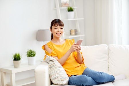 people, technology, communication and leisure concept - happy young asian woman sitting on sofa and texting message on smartphone at home 免版税图像