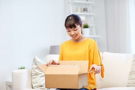 order shipment: people, delivery, commerce, shipping and shopping concept - happy asian young woman with cardboard parcel box at home Stock Photo