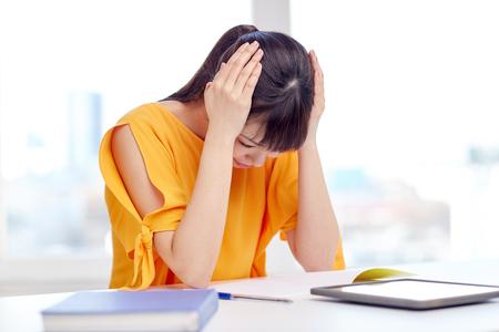 personas, de educación, de la escuela secundaria, el estrés y el concepto de aprendizaje del estudiante - mujer joven asiática cansada con el ordenador Tablet PC y el bloc de notas que sufre de dolor de cabeza en el hogar