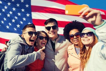 Mensen, internationale vriendschap en technologie concept - groep van gelukkige tienervrienden selfie met smartphone en duimen omhoog over Amerikaanse vlag achtergrond Stockfoto
