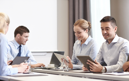 negocio, la gente y la tecnología concepto - sonriendo equipo de negocios con ordenador que cumpla Tablet PC en la oficina