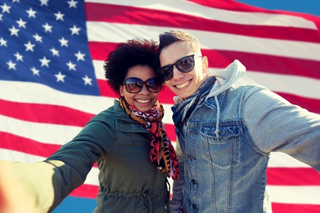 people, international friendship and technology concept - happy international teenage couple taking selfie over american flag background Stock fotó