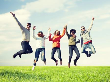 la gente, la libertà, la felicità e il concetto adolescente - gruppo di amici felici in occhiali da sole che salta sopra il cielo blu e sfondo di erba