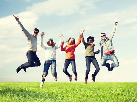 people, freedom, happiness and teenage concept - group of happy friends in sunglasses jumping high over blue sky and grass background Stockfoto