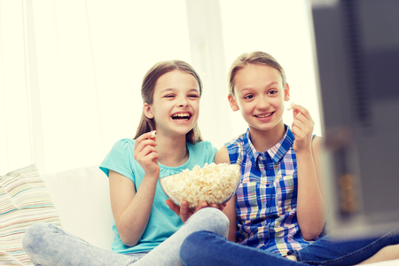 people, children, television, friends and friendship concept - two happy little girls watching comedy movie on tv and eating popcorn at home Stock Photo