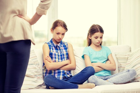 regretful: people, children, misbehavior, friends and friendship concept - upset feeling guilty or displeased little girls sitting on sofa and angry mother at home Stock Photo
