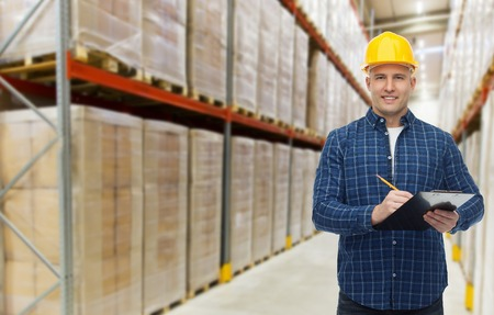 merchandise: wholesale, logistic, business, export and people concept - happy man or manager in helmet with clipboard and pencil checking goods over warehouse background