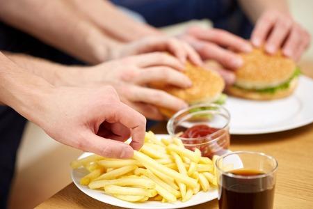 fast food, ongezond eten, mensen en junk-food - close-up van mannelijke handen met frieten en hamburgers op tafel thuis Stockfoto