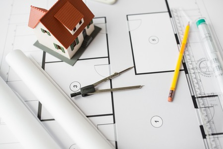 home loan: architecture, building, construction, real estate and home concept - close up of blueprint with living house model and tools