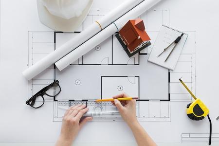 negocio, arquitectura, construcción, construcción y concepto de la gente - cerca de las manos del arquitecto con regla y lápiz de medición que viven plano de una casa