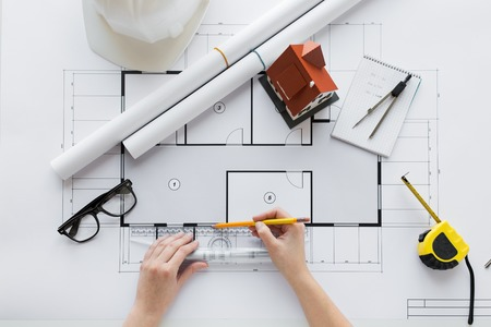 business, architecture, building, construction and people concept - close up of architect hands with ruler and pencil measuring living house blueprint Standard-Bild