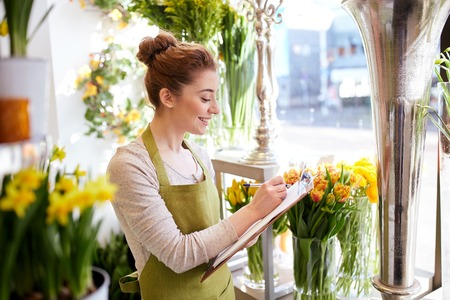 floristry: people, sale, retail, business and floristry concept - happy smiling florist woman with clipboard writing and making notes order at flower shop
