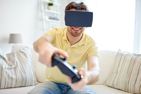 controlling: technology, gaming, entertainment and people concept - happy young man with virtual reality headset or 3d glasses with controller gamepad playing racing video game at home