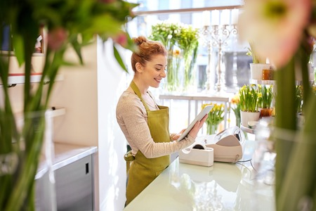 tablet: people, business, technology, sale and floristry and concept - happy smiling florist woman with tablet pc computer at flower shop