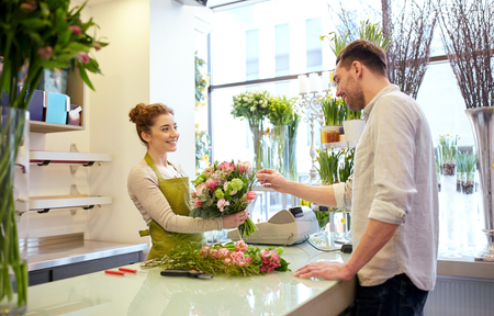 happy customer: people, shopping, sale, floristry and consumerism concept - happy smiling florist woman making bouquet for and man or customer at flower shop Stock Photo