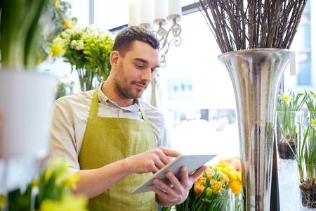 mensen, business, technologie, verkoop en bloemisterij en concept - gelukkig lachende bloemist man met een tablet pc computer op bloemenwinkel