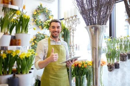 people, business, technology, sale and floristry and concept - happy smiling florist man with tablet pc computer at flower shop Zdjęcie Seryjne - 61141827