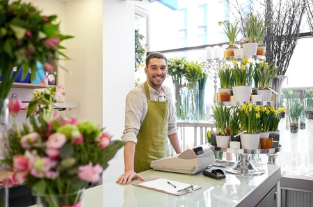 floristry: people, sale, retail, business and floristry concept - happy smiling florist man with clipboard and cashbox standing at flower shop counter