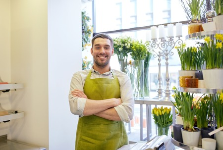 flower seller: people, sale, retail, business and floristry concept - happy smiling florist man or seller standing at flower shop counter