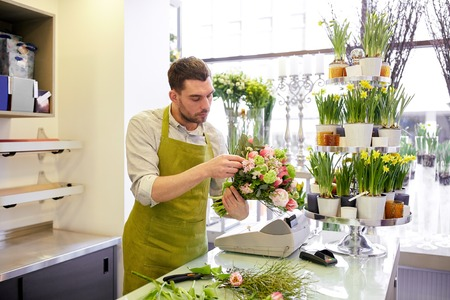 floristry: people, business, sale and floristry concept - florist man making bunch at flower shop Stock Photo
