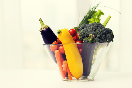 diet, vegetable food, healthy eating and objects concept - close up of ripe vegetables in glass bowl on table