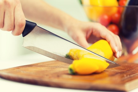 healthy eating, cooking, vegetarian food, vegetable and people concept - close up of woman hands chopping squash with knife