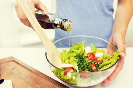 aceite de cocina: una alimentación sana, comida vegetariana, la dieta y el concepto de la gente - cerca de la mujer joven que se viste ensalada de verduras con aceite de oliva en el hogar Foto de archivo
